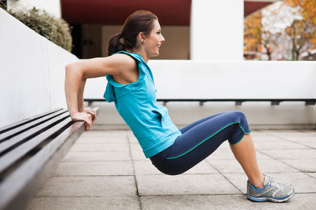Woman in sportswear performing tricep dips