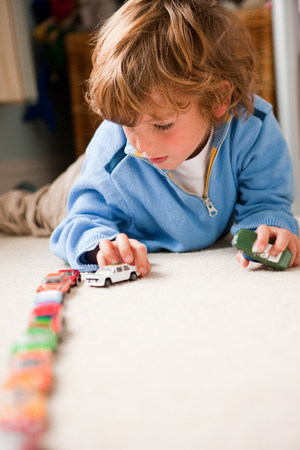 Young boy lining up toy cars in his bedroom