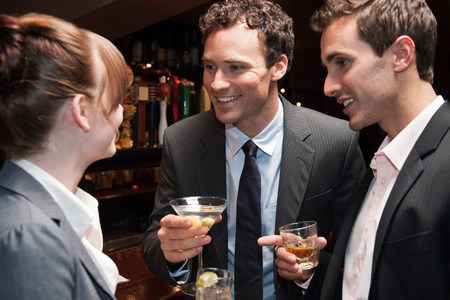 20 25 years old: Two buisnessmen chatting to female colleague at bar