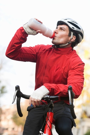 Mid adult man drinking on bicycle