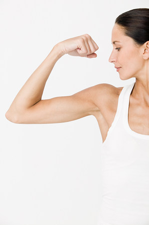 Young woman flexing muscles LANG_EVOIMAGES