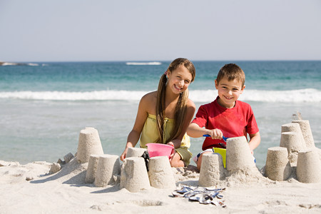 Girl and boy making sandcastles on the beach LANG_EVOIMAGES