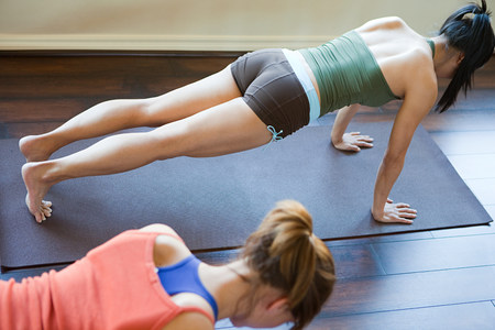 plank position: Two women doing yoga class