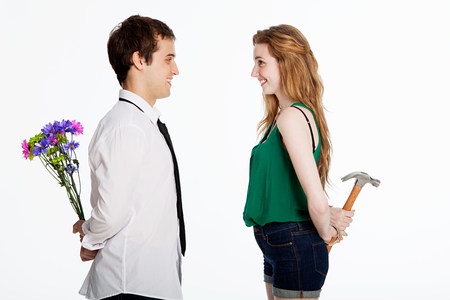 Young couple holding flowers and a hammer against white background