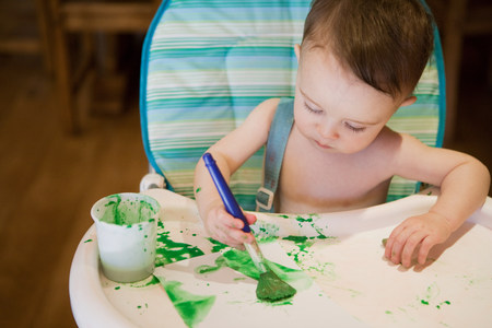untidiness: Baby boy sitting in high chair painting picture