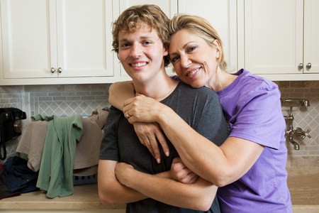 16 to 17 year olds: Mature woman and son in laundry room, portrait LANG_EVOIMAGES
