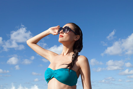 Woman wearing sunglasses shielding eyes LANG_EVOIMAGES