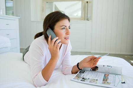 Woman home shopping on phone with credit card