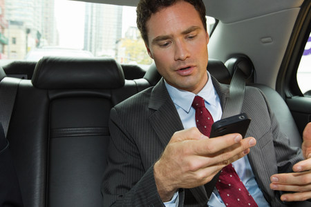 go inside: Businessman in car with smartphone
