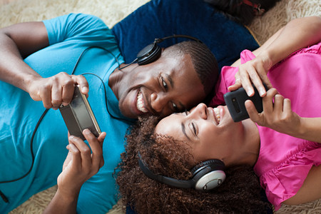 floor covering: Man and woman playing on handheld device and smartphone