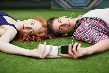 in unison: Couple lying down looking at mobile phones LANG_EVOIMAGES