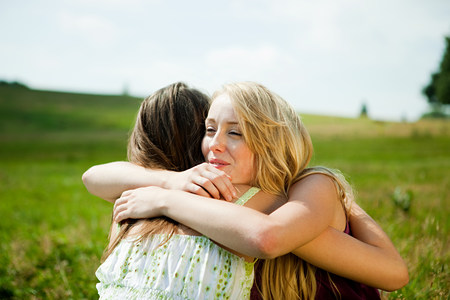 sexual intimacy: Young women embracing in a field