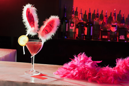 Pink cocktail, bunny ears and L plate on bar LANG_EVOIMAGES