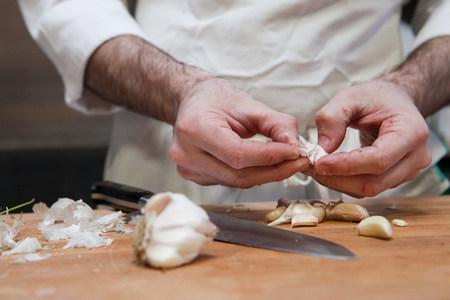 adding: Chef adding peeling garlic LANG_EVOIMAGES