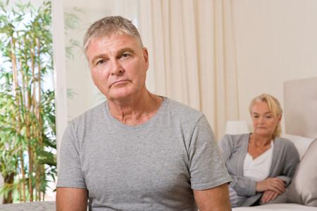 frowns: Worried couple in bedroom