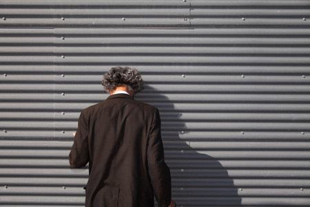 shadowed: Senior man facing wall with head downturned LANG_EVOIMAGES