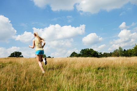 Joven mujer corriendo a través de un campo en un día soleado