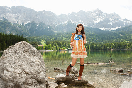 Woman with Bavarian flag, Lake Eibsee and Mount Zugspitze in background, Bavaria, Germany