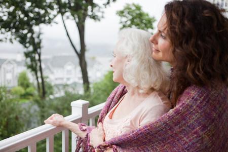 Ältere Frau und Tochter umarmt auf Veranda