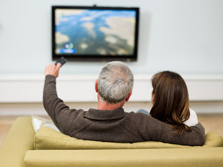 Mature couple sitting on sofa watching television LANG_EVOIMAGES