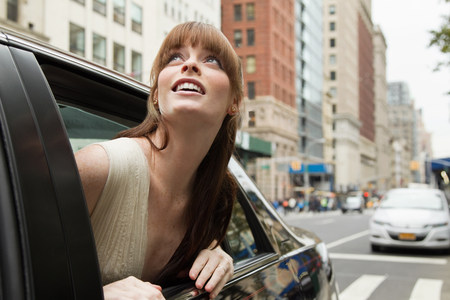 20 25 years old: Young woman leaning out of taxicab window,looking up