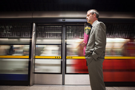 Businessman on subway platform with flowers