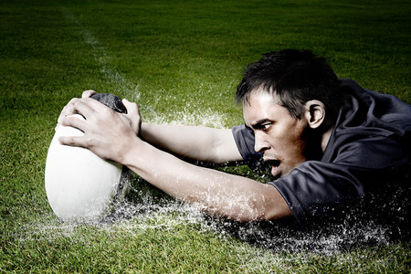 exerting: Rugby player on wet field LANG_EVOIMAGES