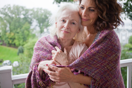 age 40 45 years: Senior woman and daughter embracing on porch, portrait