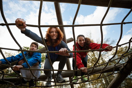 Young friends climbing assault course equipment