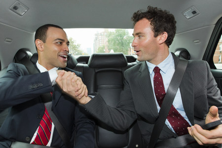 25 29 years: Businessmen shaking hands in car LANG_EVOIMAGES