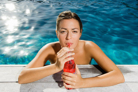 above 18: Young woman drinking soft drink at poolside