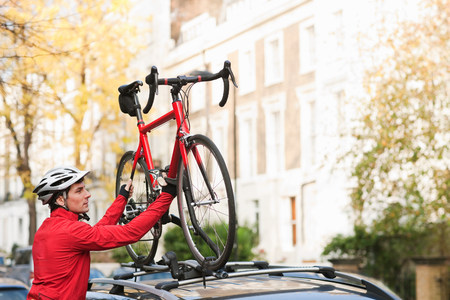 Mid adult man lifting bicycle onto car roof rack