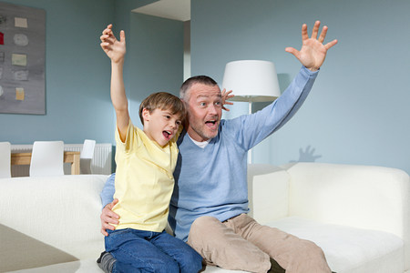Father and son watching television cheering