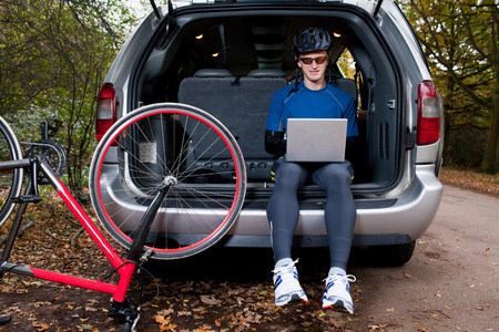Cyclist using laptop from boot of car