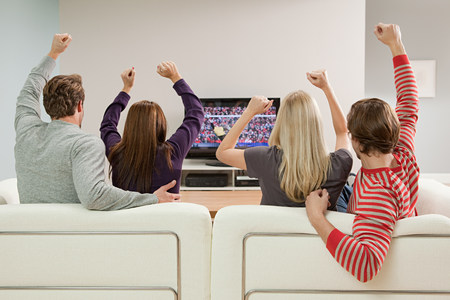 Four friends watching football on television