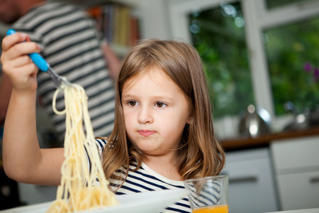 Girl holding up spaghetti at table