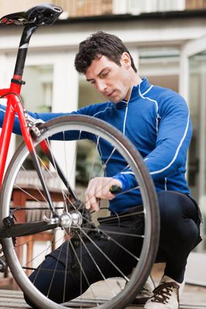 mornings: Mid adult man adjusting bicycle wheel