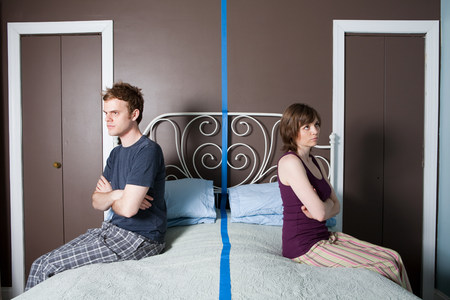 exasperation: Young couple sitting on bed separated by blue line
