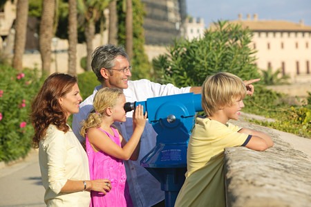 Family using telescope to look at view