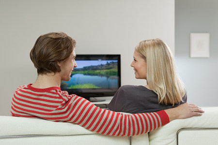 arms behind head: Couple watching television
