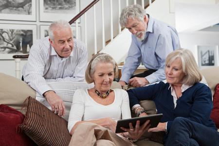 60 64 years: Senior friends using digital tablet