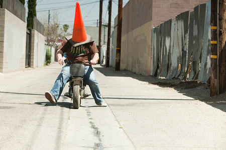 context: Man with traffic cone on head, riding motorbike
