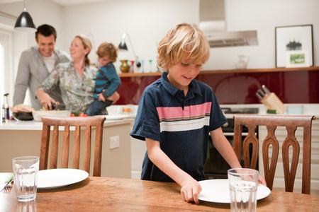 relaciones laborales: Hijo ayudando a poner la mesa con los padres y el hermano visible detrás de la cocina