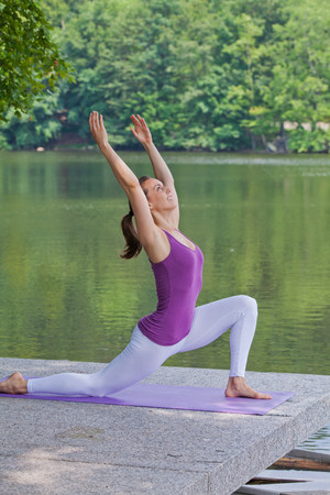 Mid adult woman performing yoga by river LANG_EVOIMAGES