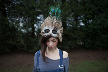 kooky: Young woman with feathered mask on her head