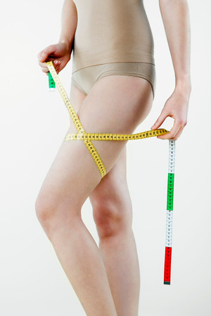 narcissist: Young woman measuring thigh with tape measure