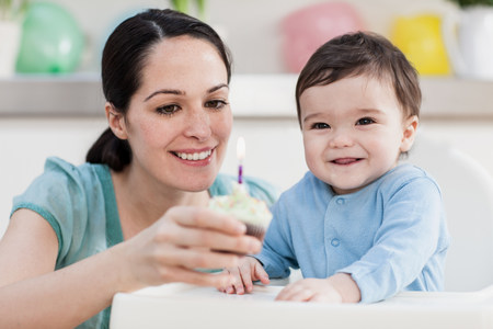 Mother giving birthday cupcake to baby son