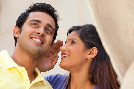 Woman whispering in a mans ear