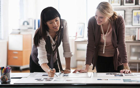 Two creatives studying designs on desk