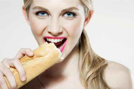 20 25 years old: Young woman biting baguette LANG_EVOIMAGES